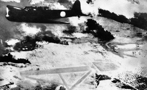 a-japanese-bomber-on-a-run-over-pearl-harbor-hawaii-is-shown-during-the-surprise-attack-of-dec-7-1941-black-smoke-rises-from-american-ships-in-the-harbo